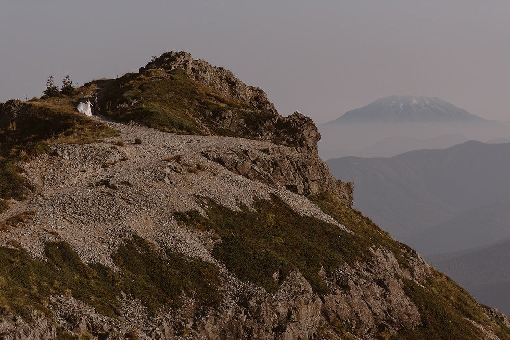 A bride and groom can be seen hiking in the distance on the steep side of a rocky, granite mountain that's peppered with green moss. In the distance, an enormous mountain peak looms through the fog.