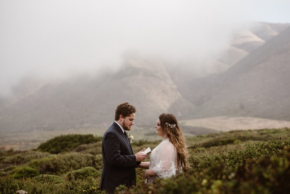 A bride and a groom stand among a lush Oregon meadow as they read their vows to each other. These elopement photos were captured as part of a destination elopement ceremony captured by Oregon elopement photographers Adventure Instead
