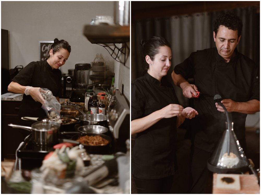 Two private chefs hustle and bustle around the kitchen to prepare a private, gourmet dinner for the bride and groom as part of their party after eloping. In the photo on the right, a female chef dumps food into a pan. In the elopement photo on the right the two chefs light a piece of brie cheese inside a glass beaker to melt it.