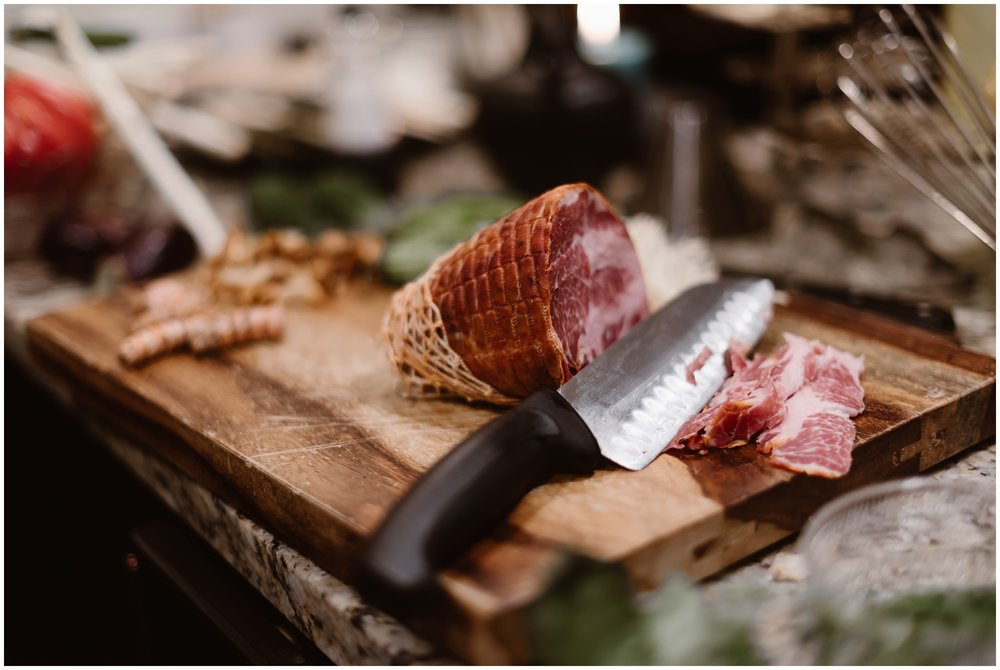 A piece of charcuterie meat lays on a wooden cutting board. The sliced prosciutto has a sharp knife laying next to it. This is part of the gourmet meal that Katie and Logan wanted for their reception after eloping. These adventure elopement photos were captured by elopement wedding photographer Adventure Instead.