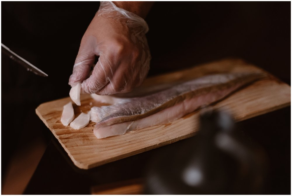 With a gloved hand, a private chef prepares a gourmet cut of fish by filleting it carefully on a wooden board. This food will be enjoyed by the bride and groom as a part of their reception after eloping in the Colorado mountains.