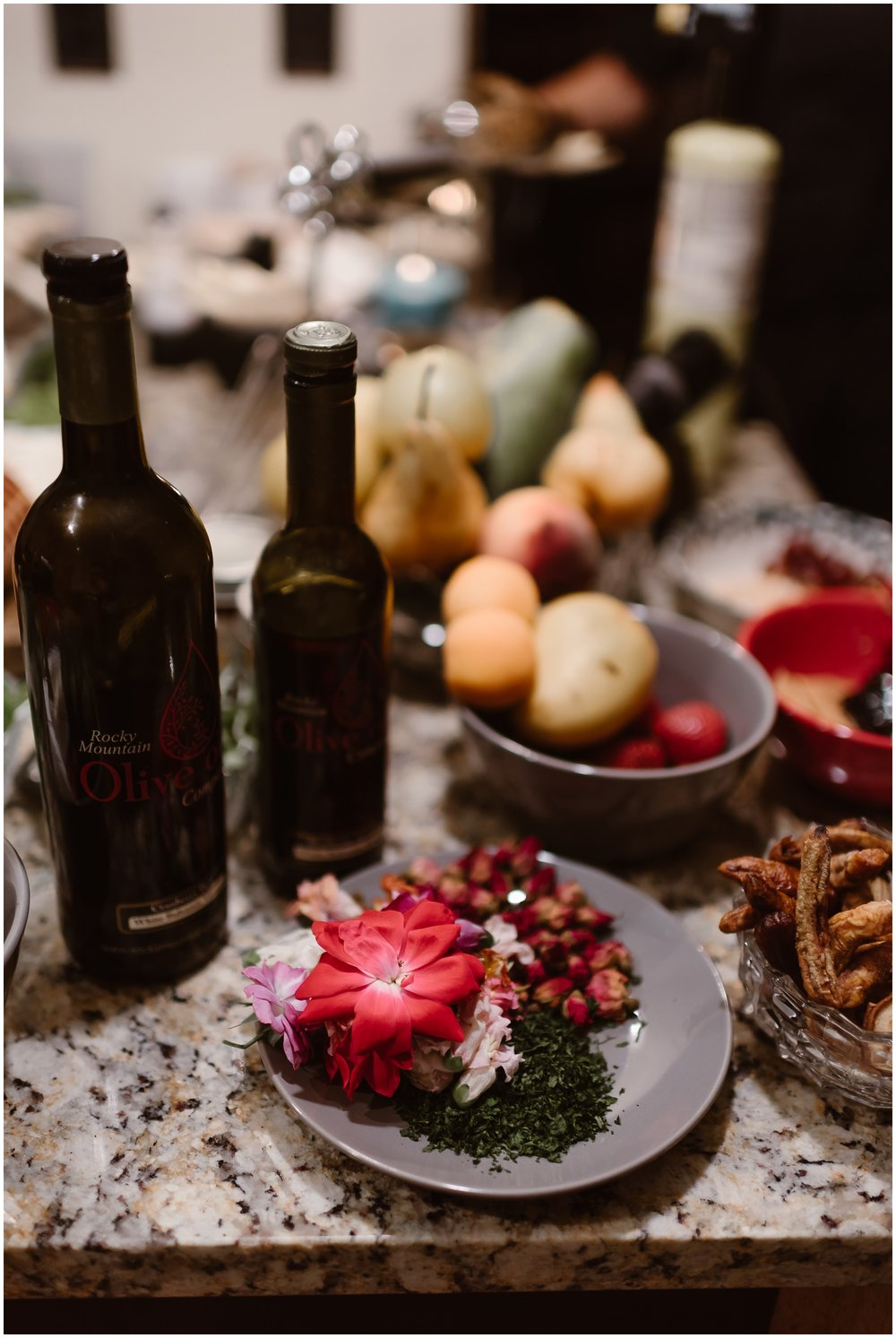 A beautiful arrangement of garnishes sits on a plate on top of a marble counter top. These spices, garnishes, and nearby bottles of wine are all a part of the gourmet dinner that the bride and groom wanted as part of their small simple wedding. For their party after eloping, they hired two private chefs.