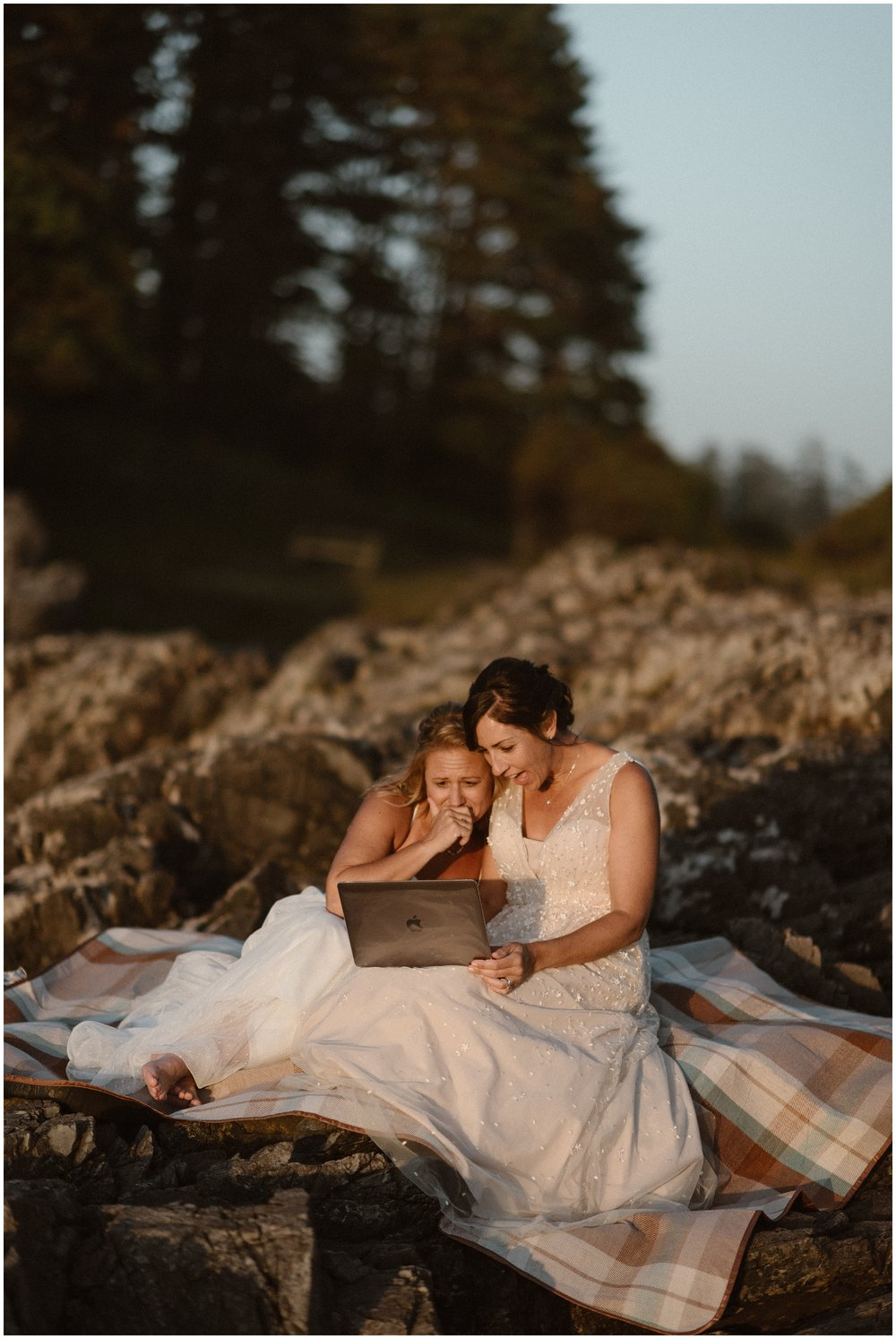 Two brides sit on a rocky ledge on top of a tan and blue plaid blanket with a laptop on their laps. One bride holds her hand up to her mouth, holding back emotion, while the other bride opens her mouth wide in surprise. Skyping or FaceTiming with family is a great way to elope with immediate family without them actually being present for your ceremony.