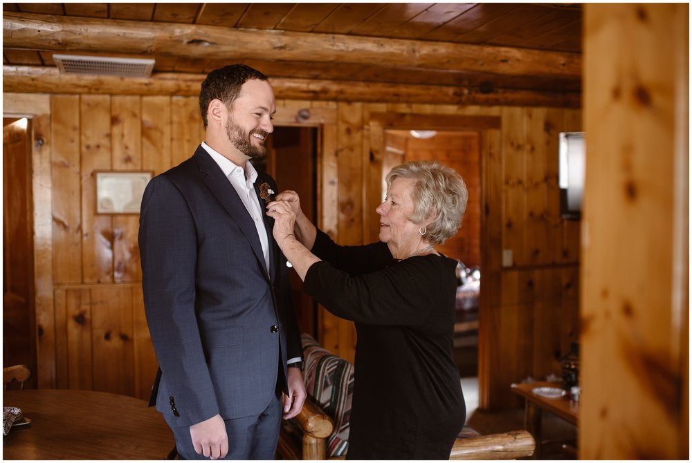 A mother pins a boutonniere to her son's tux while helping him get ready for his elopement wedding. The two stand in a wooden cabin room, smiling at each other in these family wedding photos that were captured by elopement photographer Adventure Instead./
