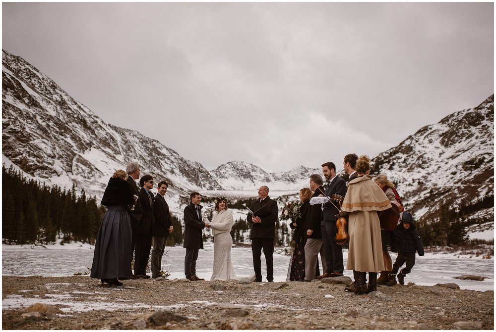 A bride and groom stand in the presence of their friends and family and an officiant. All of them, in formal (but warm) winter clothes are standing next to a frozen mountain lake. Snow-covered granite mountains loom in the background in these family wedding photos, which were captured by elopement photographer Adventure Instead.
