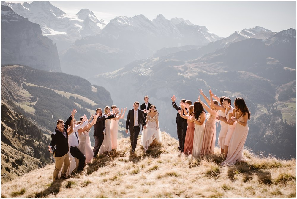 A bride and groom finish up their elopement ceremony at the top of a mountain. About 10-15 people are at their elopement ceremony and there's an officiant in the background . Behind them, tall mountain ranges are looming. Eloping with family can be an amazing way to capture adventure and a small simple wedding all at once.