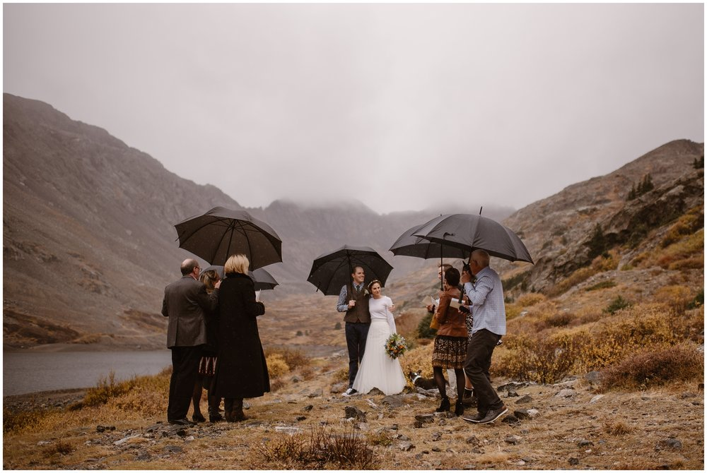 A bride and groom stand close together, tucked under an umbrella in a misty, foggy location during their elopement ceremony. With them are about 6-10 people. This is a beautiful example of eloping with close family while still having a small intimate wedding.