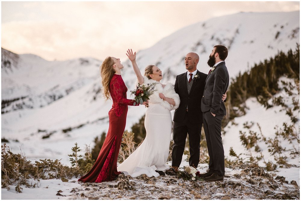 A bride and a groom stand on a snow mountaintop with a woman in a red dress (presumable a bridesmaid) and another man in a tux. The bride, hands in the air, poses excitedly during their small, simple wedding. This is one of the perfect examples of how to have a small wedding—the two of you and the people who are closest to you.