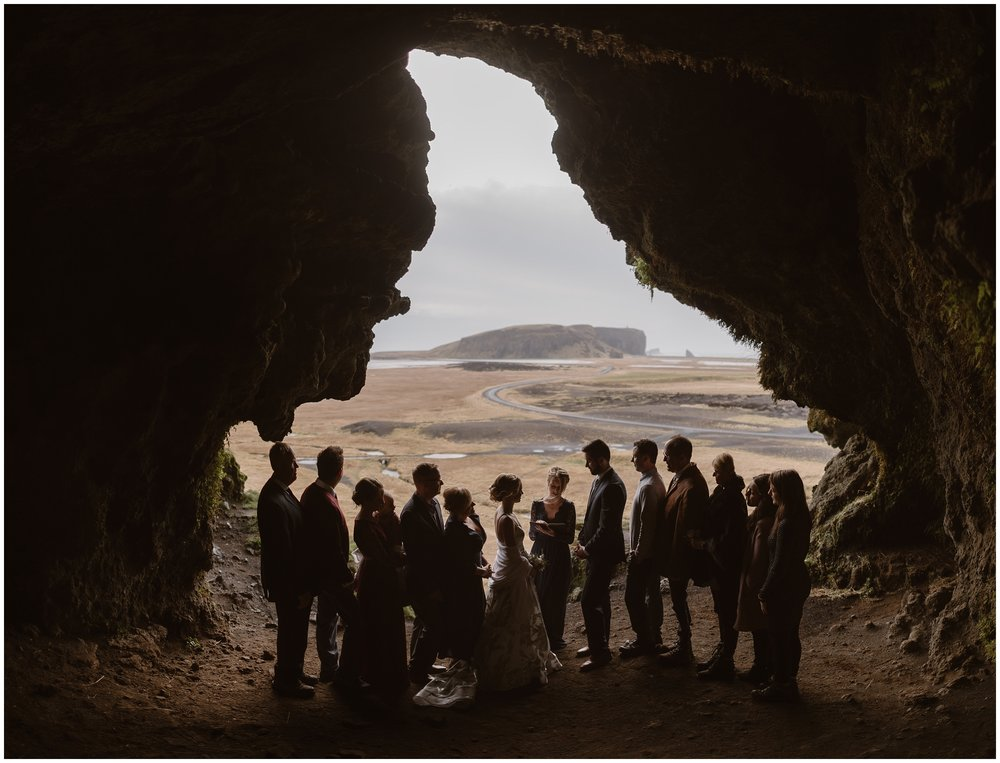 A bride, a groom, and about 10 guests are silhouetted in a beautiful cave during their elopement ceremony. This small wedding idea includes eloping with close family, which is a beautiful and meaningful way to reap the benefits of eloping while including the one who mean the most to you.