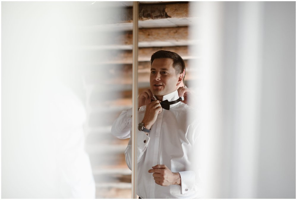 The grooms helps each other finish up their final touches during their time getting ready together. One groom helps his soon-to-be husband adjust and tie his peacock bow tie before they get ready to leave for their Colorado mountain wedding.