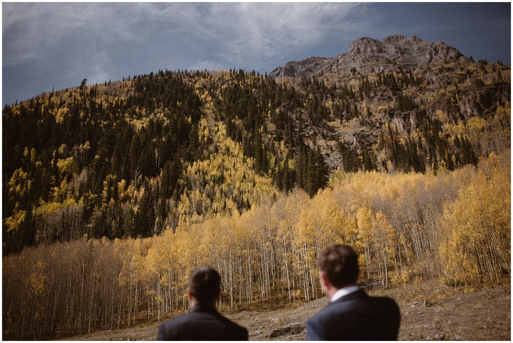 In these elopement photos captured by Adventure Instead, a Colorado elopement photographer, Brian and Ernie (the soon-to-be married couple) gaze out at the golden and yellow aspen trees blooming in a grove at the base of an Ouray, Colorado mountain. This location was one of the small wedding ideas that the couple had for their Colorado mountain wedding.