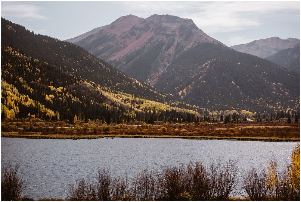 A golden and green mountain looms in the background of a gorgeous, sparkling lake. This image—captured by Adventure Instead, a Colorado elopement photographer— shows Ouray, Colorado during its peak Fall season, a location that's one of the best elopement ideas.