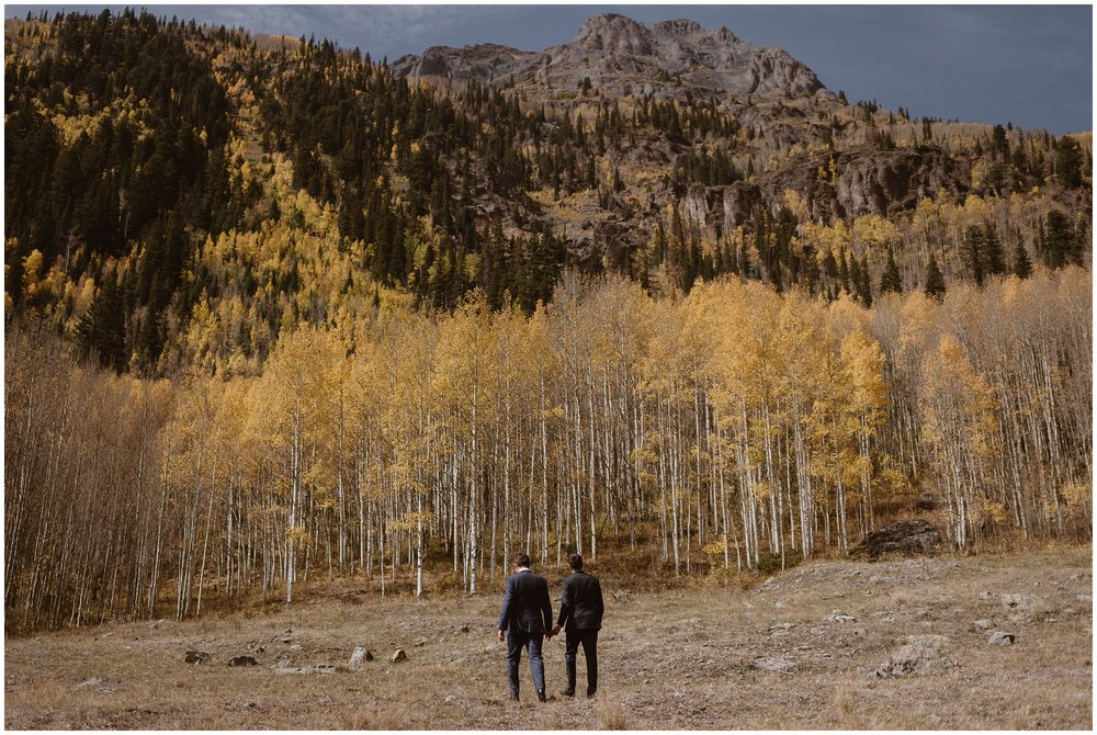Brian and Ernie, in their dark tuxes, stand among a vibrant yellow and gold Aspen grove. In the distance, green and gold trees dot a rocky mountain in Ouray, Colorado. This destination elopement spot was the perfect choice for Brian and Ernie as they'd grown up working summers here.