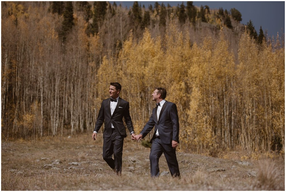 Brian and Ernie, the two grooms, take hands as they explore an aspen grove in Ouray, Colorado before their elopement ceremony. These elopement photos were captured by elopement wedding photographer Adventure Instead.