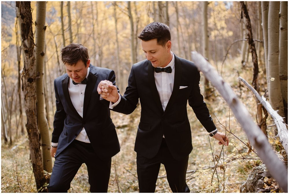 Brian and Ernie take hands as they traipse through an aspen grove together before their Colorado mountain wedding. These elopement photos, captured by Adventure Instead, show the striking gold and yellow aspen trees in Ouray, Colorado, and were a part of Brian and Ernie's unique eloping ideas for their small simple wedding.