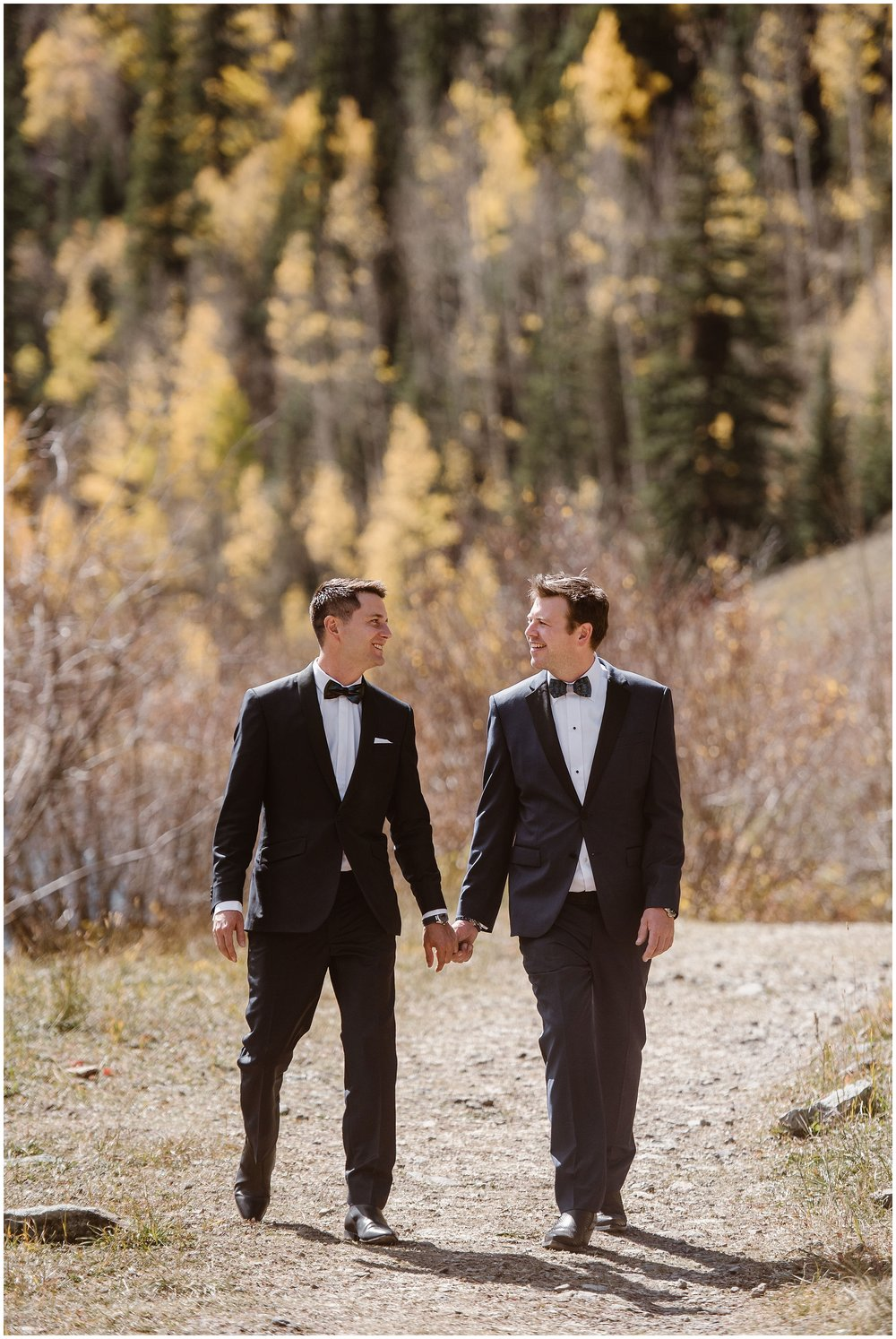 Brian and Ernie take hands as they walk away from a gorgeous, vivid aspen grove toward their elopement ceremony. As part of ther small, simple wedding, Brian and Ernie chose to incorporate one of their unique eloping ideas — renting side-by-sides to take them up the mountain to their destination elopement.