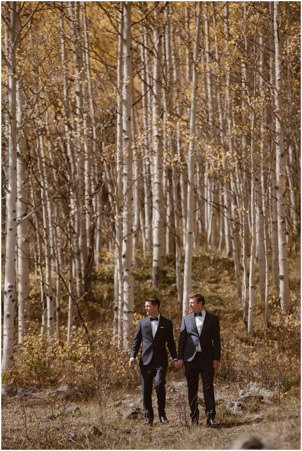 The two grooms, Brian and Ernie, hold hands in the middle of a golden Aspen grove during their fall Colorado mountain wedding. These elopement photos were captured before their elopement ceremony in Ouray, Colorado.