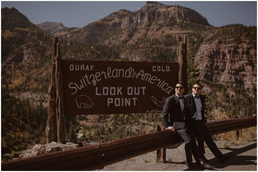 """The two grooms, Brian and Ernie, stand in front of a mountain range and a sign that states """"Ouray, Colorado. Switzerland of America."""" The two of them wear their suits for their elopement ceremony and have dark black sunglasses on."""