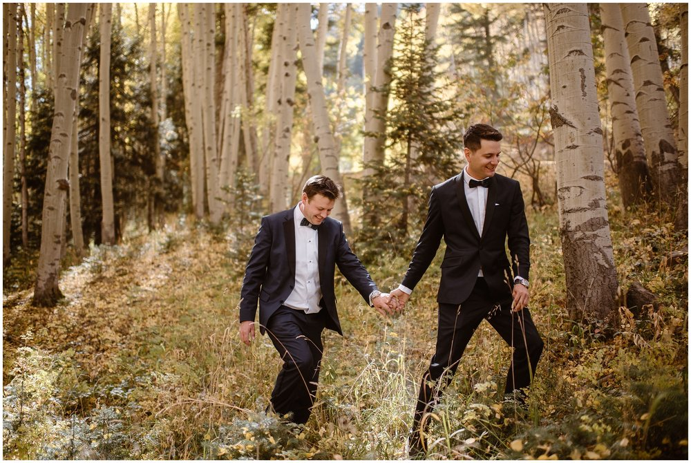 The two grooms take hands as they walk through a golden aspen grove toward their Colorado mountain wedding elopement ceremony spot. Their 4x4 wedding required off-road vehicles to reach the location for their destination elopement.