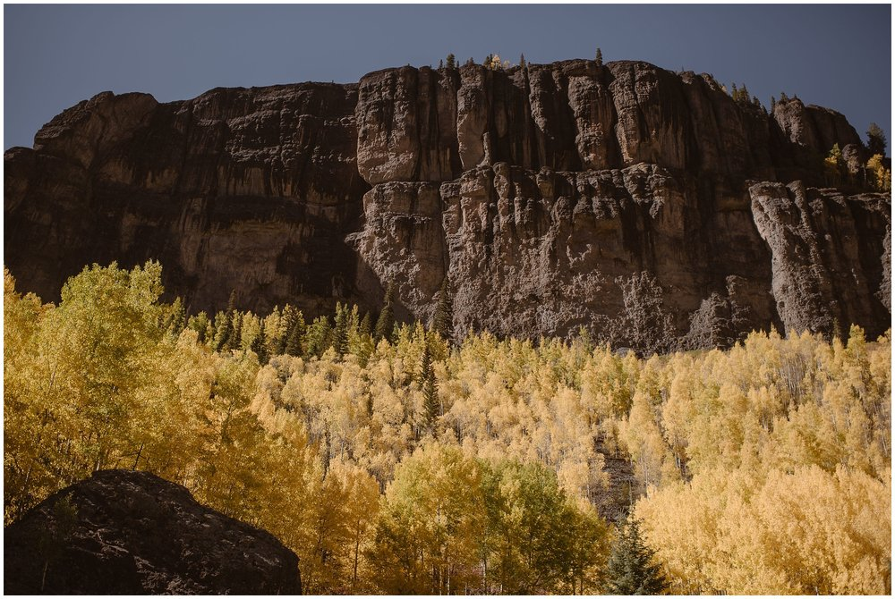A giant, jagged mountain face is shown in stark contrast to the golden grove of aspen trees growing at its base. These elopement photos were captured by elopement wedding photographer Adventure Instead.