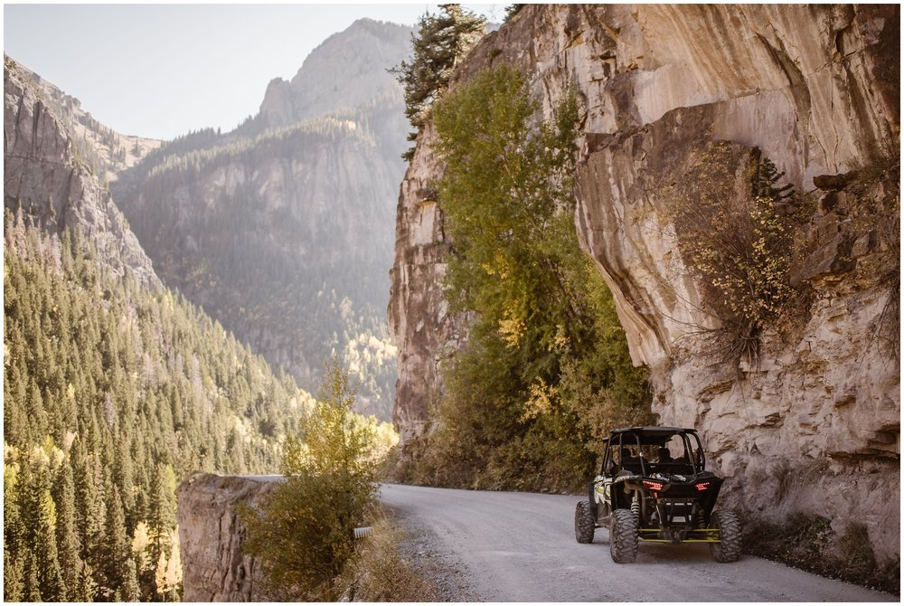 The side-by-side vehicle is shown driving up a 4x4 road in Ouray, Colorado. As the side-by-side zips up the 4x4 road, vibrant green and gold trees can be seen from the steep road drop-off.