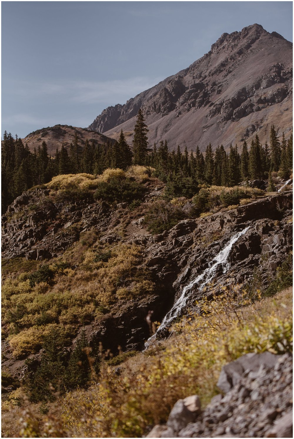 A small, but powerful, waterfall, trickles down the rocks on the Ouray, Colorado mountainside. In the background, green and yellow trees, golden foliage, and craggy mountains can be seen. This is one of the most beautiful places to elope in Colorado.