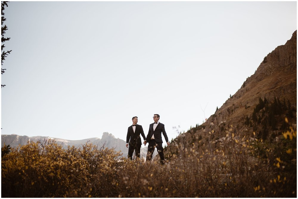 Brian and Ernie stand among a field of golden, Fall wildflowers as they hold hands and make their way toward their elopement ceremony spot. These elopement photos were captured by Adventure Instead, an elopement wedding photographer.