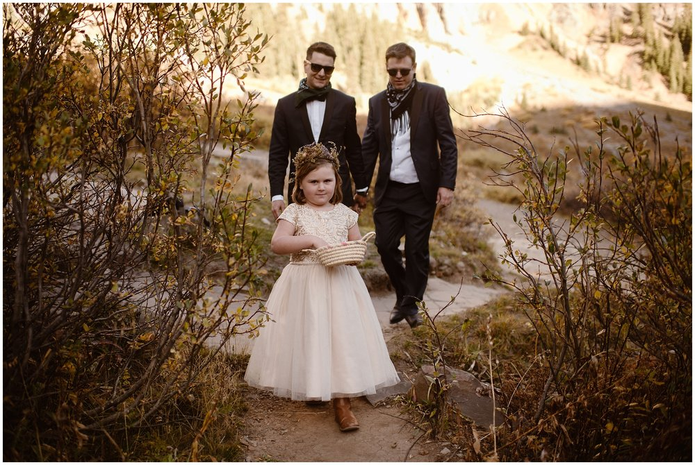Brian and Ernie, the two grooms, walk behind their young niece as she throws petals in front of them. The flower girl is wearing a cute, white dress with lots of frills in this elopement photo. She reaches into her basket for more petals to lead off the elopement ceremony.