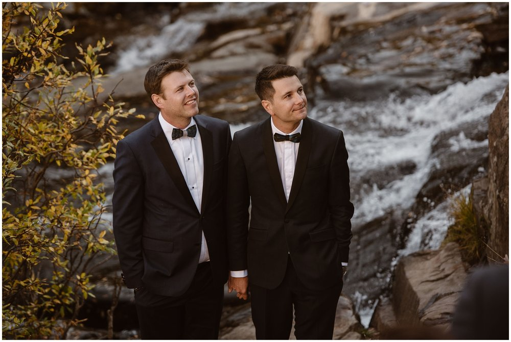 The two grooms stand at the base of a gorgeous waterfall and hold hands as their family members lead them through a customized, intimate elopement ceremony during Brian and Ernie's 4x4 elopement.