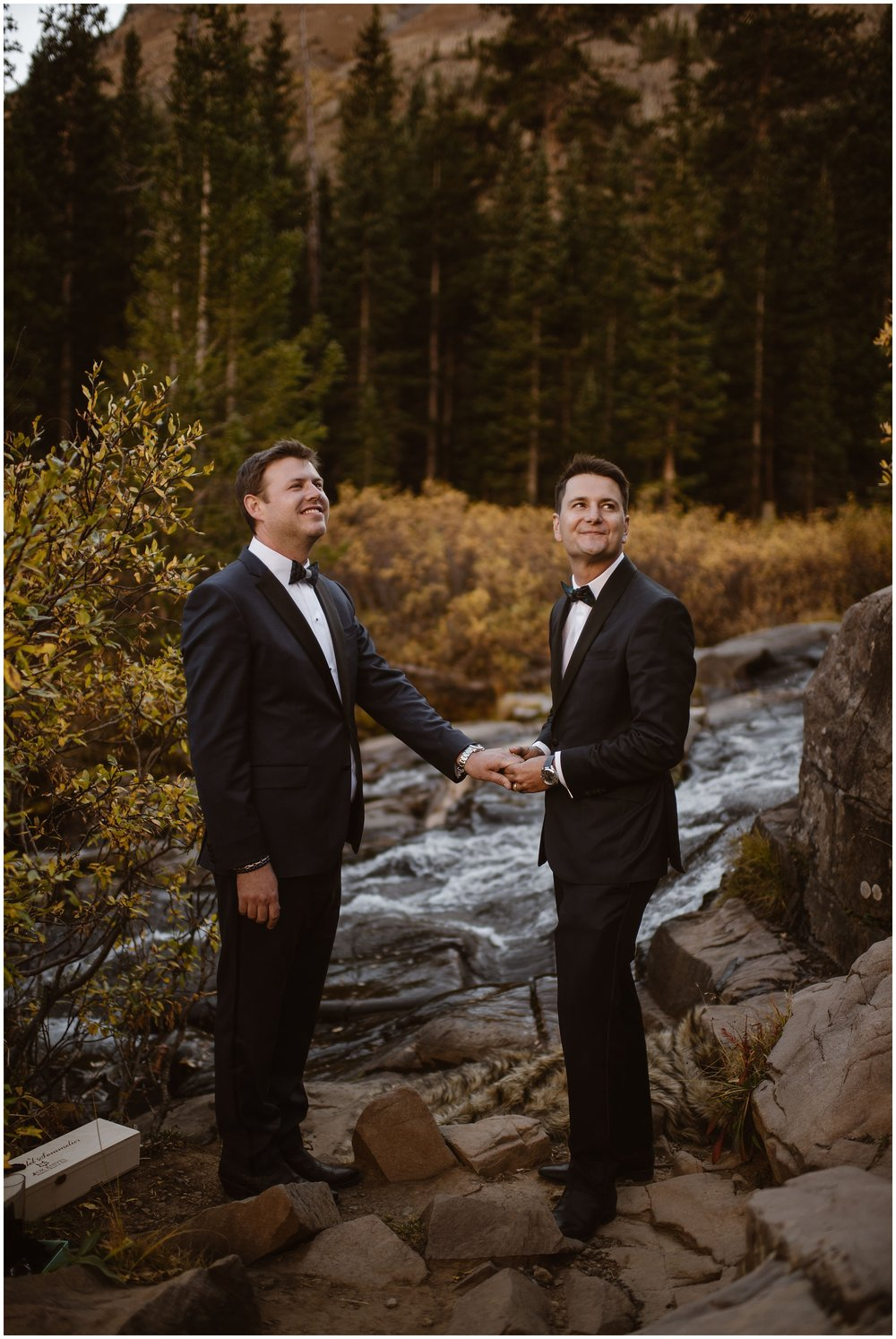 The two grooms, Brian and Ernie, hold hands as they stand at the base of a gorgeous waterfall as their family leads them through a unique elopement ceremony . Choosing to have a private ceremony followed by a family-oriented ceremony is one of the best elopement ideas a couple can include in their special day.