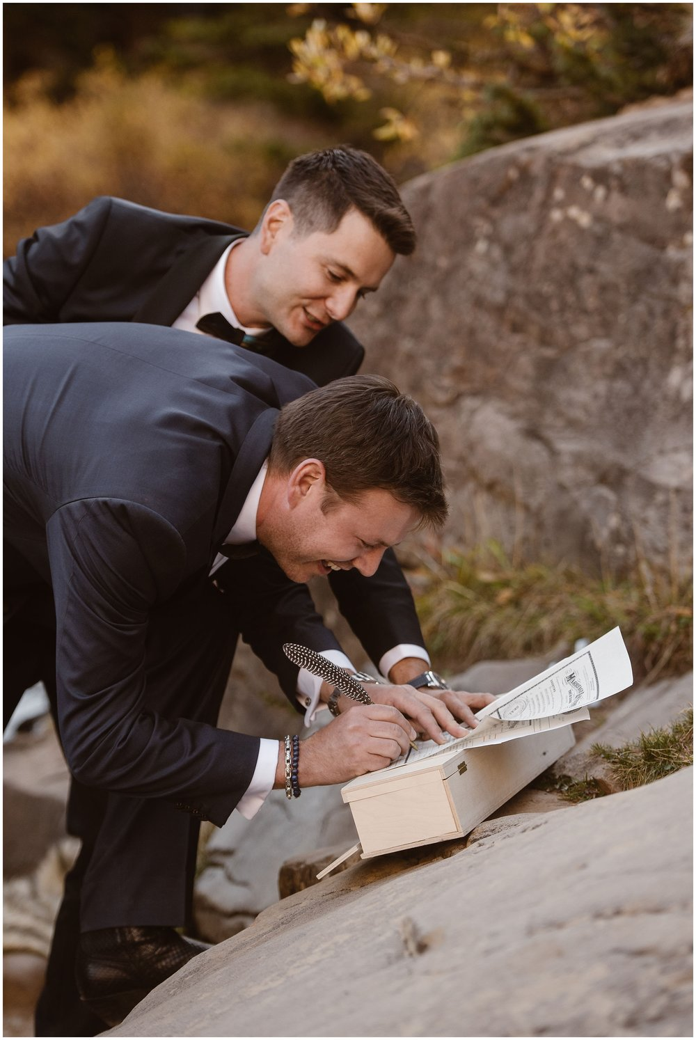 Brian and Ernie lean down to sign their marriage license with their feathered, quill pen. The two smile as they take turns signing this as the final part of their elopement ceremony.