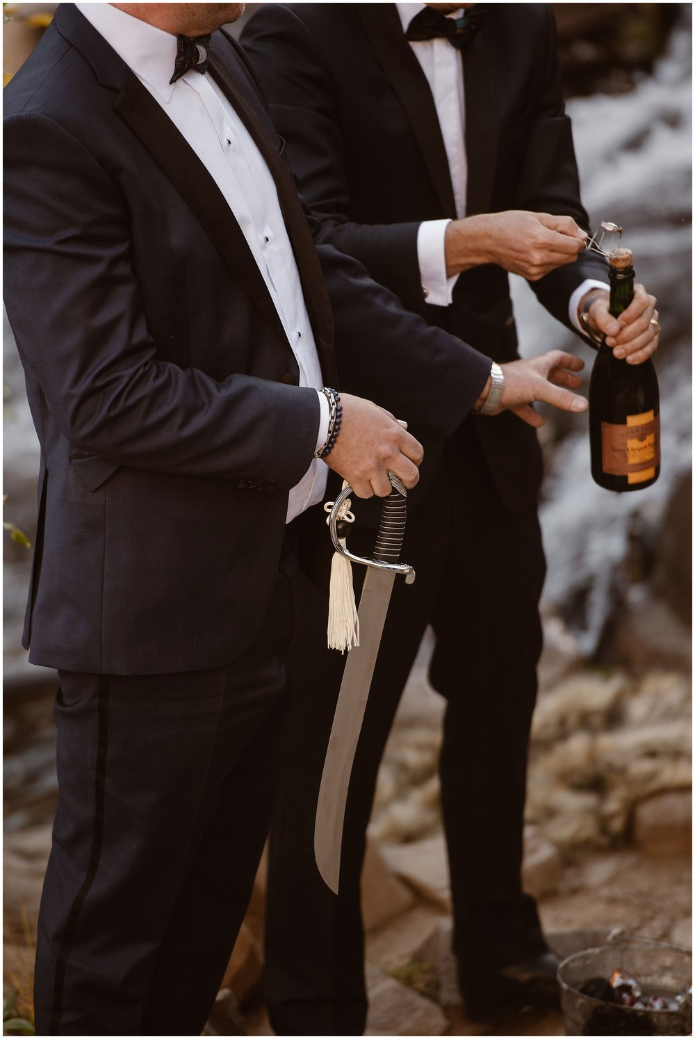 The newlywed couple holds a bottle of champagne and a Samurai sword in their hands after their elopement ceremony. Brian and Ernie planned to incorporate one of their unique eloping ideas into their small simple wedding — cutting the champagne cork off with a sword.