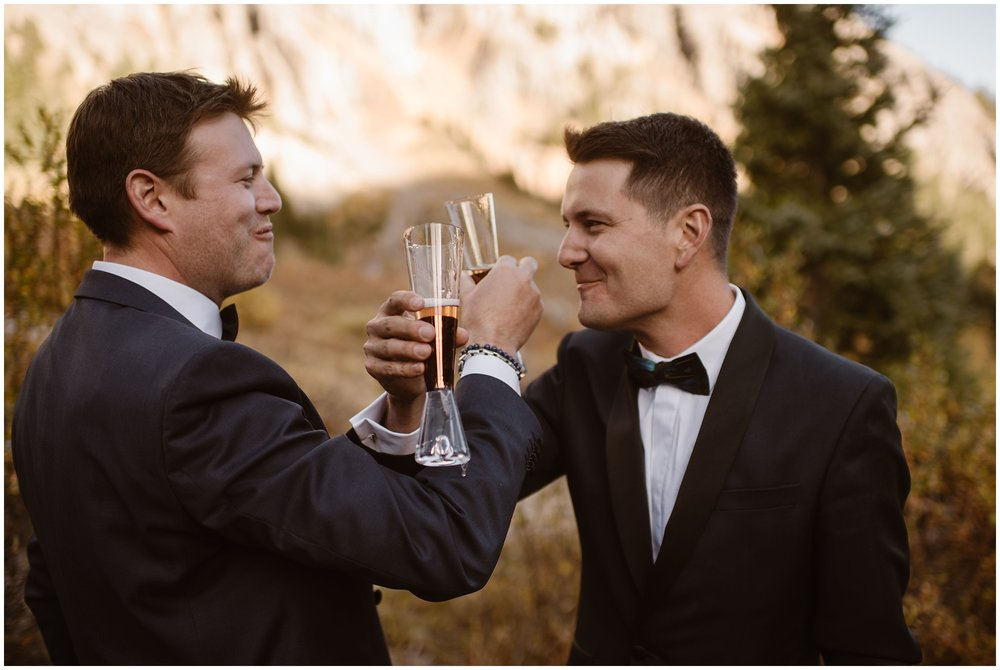 The newlyweds Brian and Ernie link their arms as they hold their champagne glasses, toasting their elopement ceremony. This was just one of their unique eloping ideas for their 4x4 elopement in the San Juan Mountains.