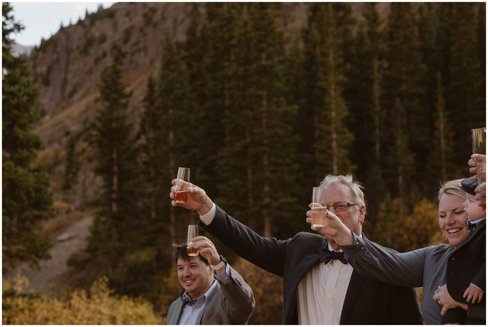 The guests at Brian and Ernie's wedding hold up their glasses of champagne to toast to the happy, newly wedded couple. This Colorado mountain wedding incorporated some of the best elopement ideas that Brian and Ernie could come up with, including eloping with family and having their own, private elopement ceremony.