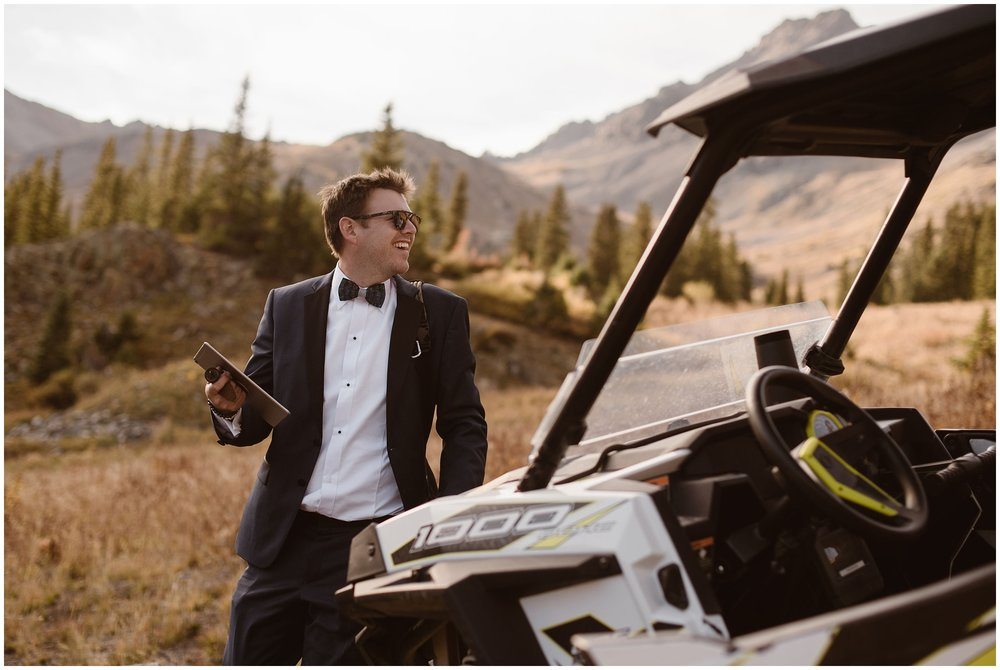 One of the grooms packs up his items and heads back toward the side-by-side vehicle to zoom back down the mountain with his new husband. The two chose a 4x4 elopement for their Colorado mountain wedding so they could elope in their ideal location.
