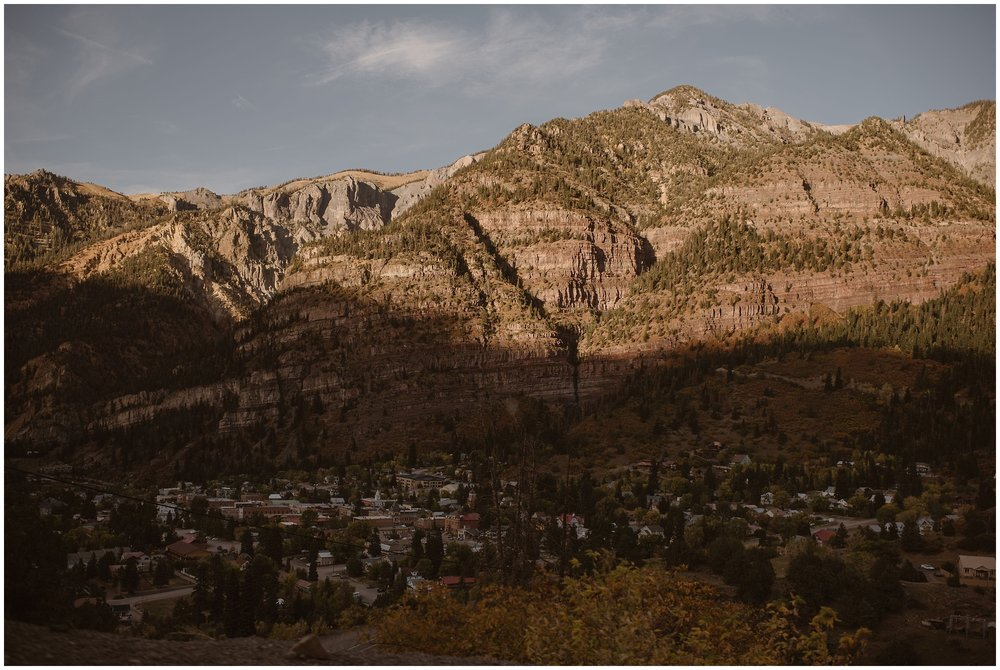 The sun begins to set on the multi-colored Ouray, Colorado mountain range. The base of the mountain and downtown Ouray is cast in shadows in this elopement photo taken by Adventure Instead, an elopement wedding photographer.