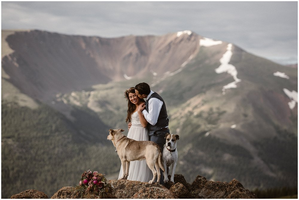 A bride and groom embrace each other as they stand on a cliff during their elopement ceremony. The best part? Their two dogs stand right next to them with giant mountain ranges peeking in the background. Wedding photos with dogs, and including your dog in wedding ceremony is totally doable during an adventure elopement!