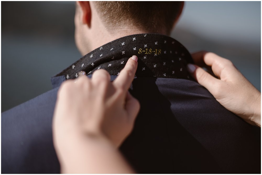 Lauryn flips up the collar of her soon-to-be-husband's custom suit to reveal the day's date stitched into it. Including small details in your elopement makes for some of the best elopement photos.