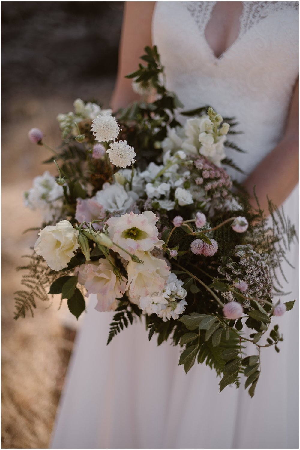 Lauryn shows off her beautiful, custom bouquet of flowers — this is always one of the best elopement ideas to include in your small simple wedding. Lauryn's bouquet includes beautiful white, light pink, and green foliage, a very PNW bouquet.