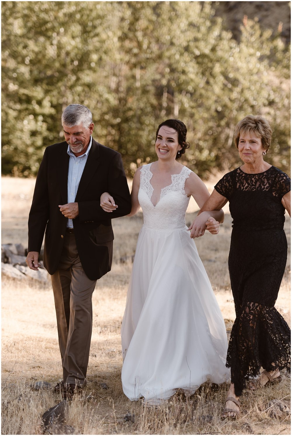 Lauryn's mom and dad hold her hands on either side and walk her toward her elopement ceremony. With her dad on her right and her mom on her left, they stride toward where David is waiting for them.