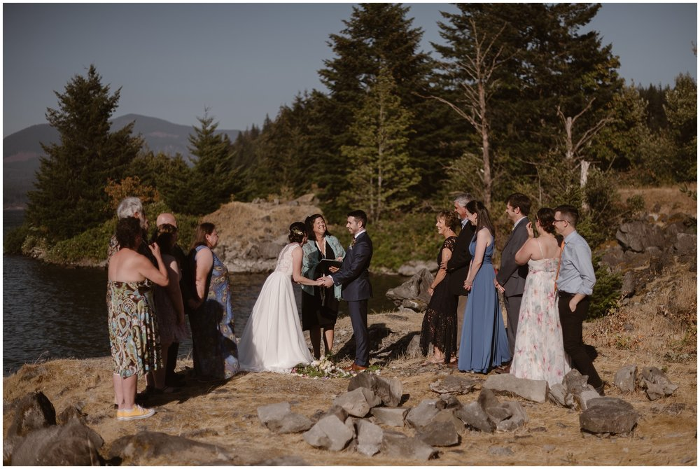 On a cliff side on the Columbia River Gorge, Lauryn and David, the bride and groom, stand in the middle of a floral circle while an officiant marries them in front of about 10 of their closest friends and family. One of their unique eloping ideas was to have a family elopement ceremony in Oregon, standing among the dark green trees along the Columbia River.