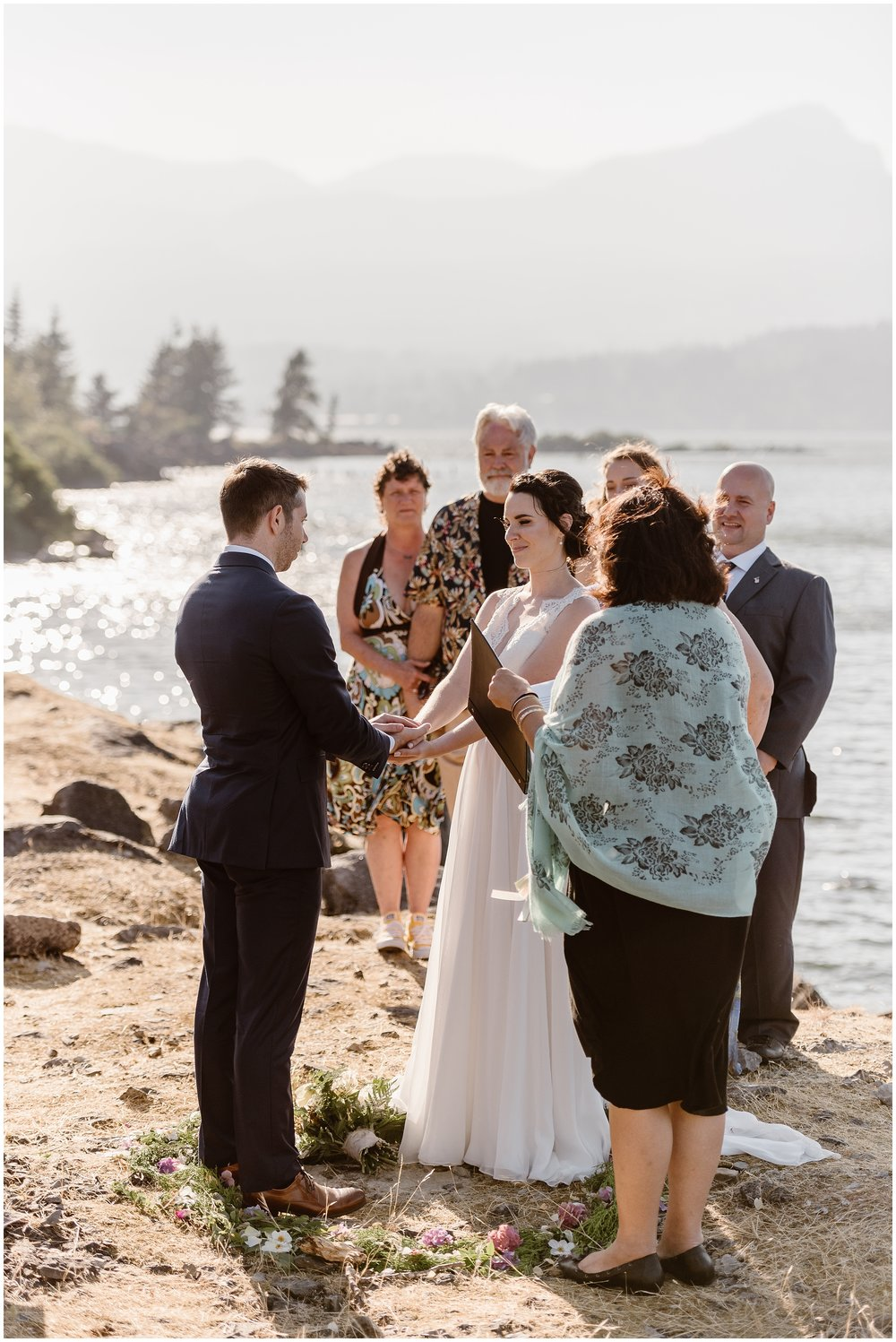The bride and groom, Lauryn and David, stand in the middle of a floral circle on the ground on the side of the rushing Columbia River. Their elopement ceremony took place in the Columbia River Gorge surrounded by family and filled with their own unique eloping ideas.