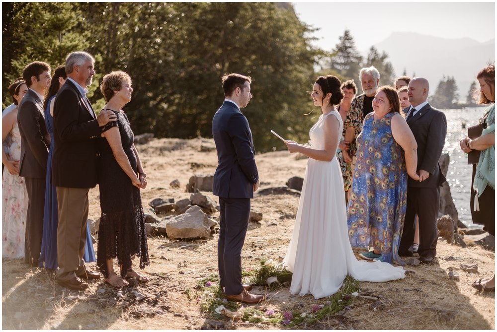 Lauryn, the bride, reads her vows to her soon-to-be-husband David with their 10 closest friends and family surrounding them during their Columbia River Gorge elopement.