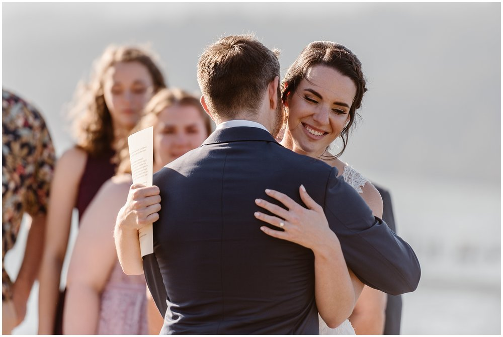 The bride and groom embrace during their elopement ceremony right after the bride, Lauryn, finishes reading her vows to David, the groom. Behind them, the rushing Columbia River and their closest friends and family can be seen.