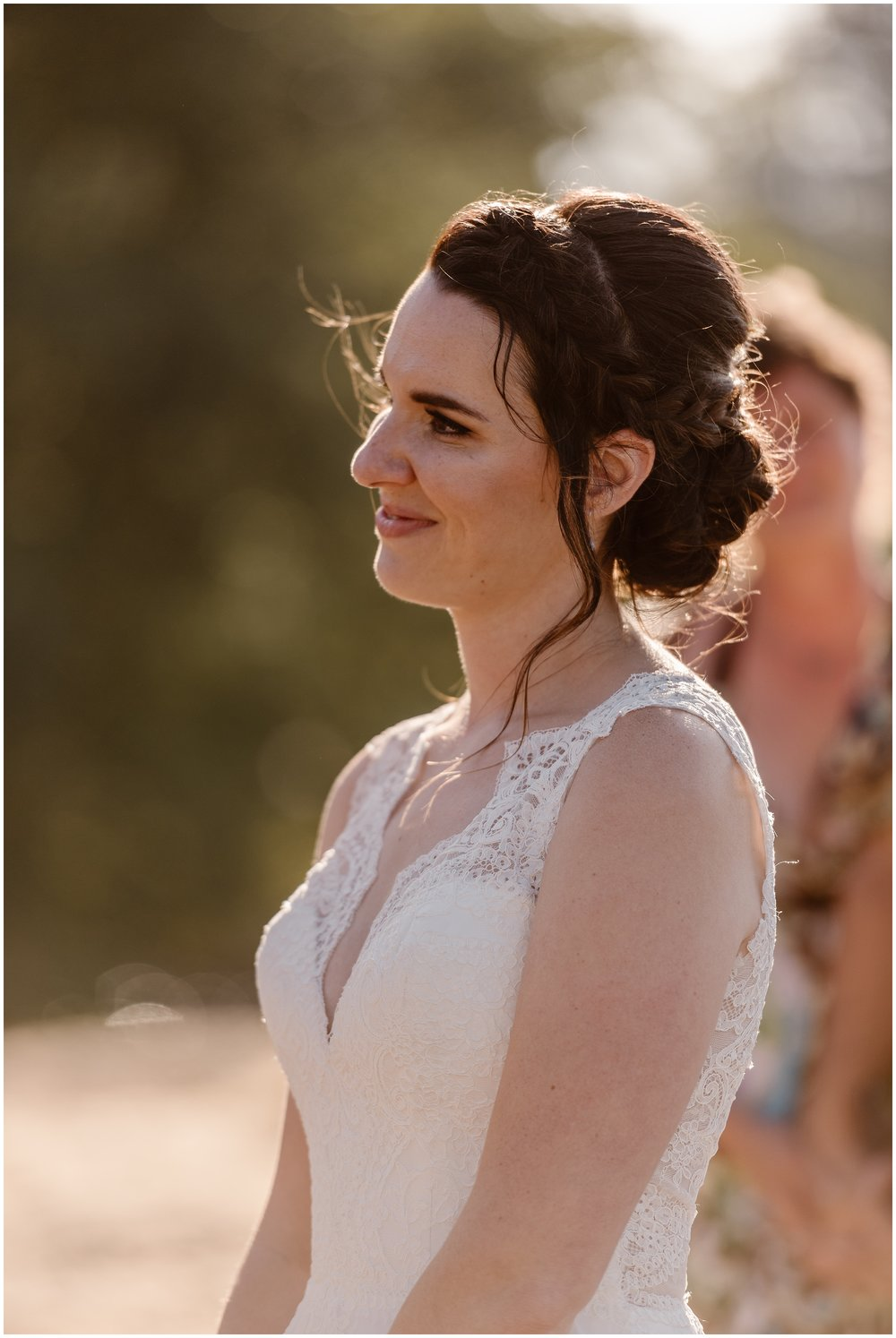 In this elopement photo captured by Adventure Instead (an Oregon elopement photographer) , the bride, Lauryn is shown looking and smiling at her groom, David. Lauryn is dressed in a cream-colored, lace wedding gown and her hair is braided back into a bun.