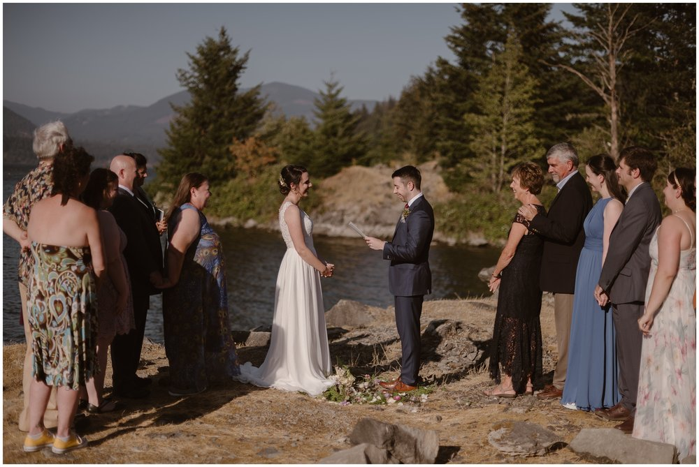 The bride and groom stand within the flower circle they built for their elopement ceremony as David, the groom, reads his vows to Lauryn. Their Columbia River Gorge wedding included about 10 members of their family, and all can be seen here as they stand on the bank of the Columbia River during their Oregon elopement.