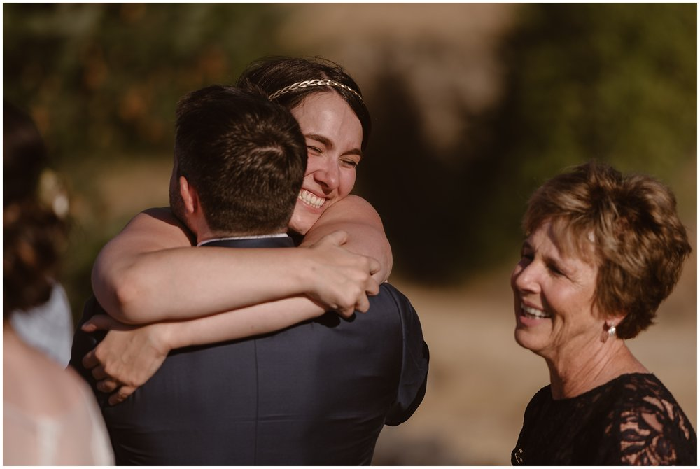 Family members hug the groom, David, as they party after eloping. Everyone is celebrating, hugging, and cheering after the Columbia River Gorge wedding.