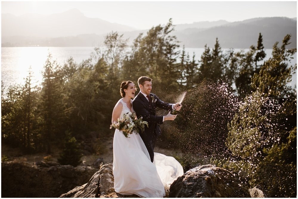 At the top of a craggy rock, with the Columbia River and PNW islands dotting the river behind them, Lauryn and David pop a bottle of champagne to celebrate their Columbia River Gorge wedding.