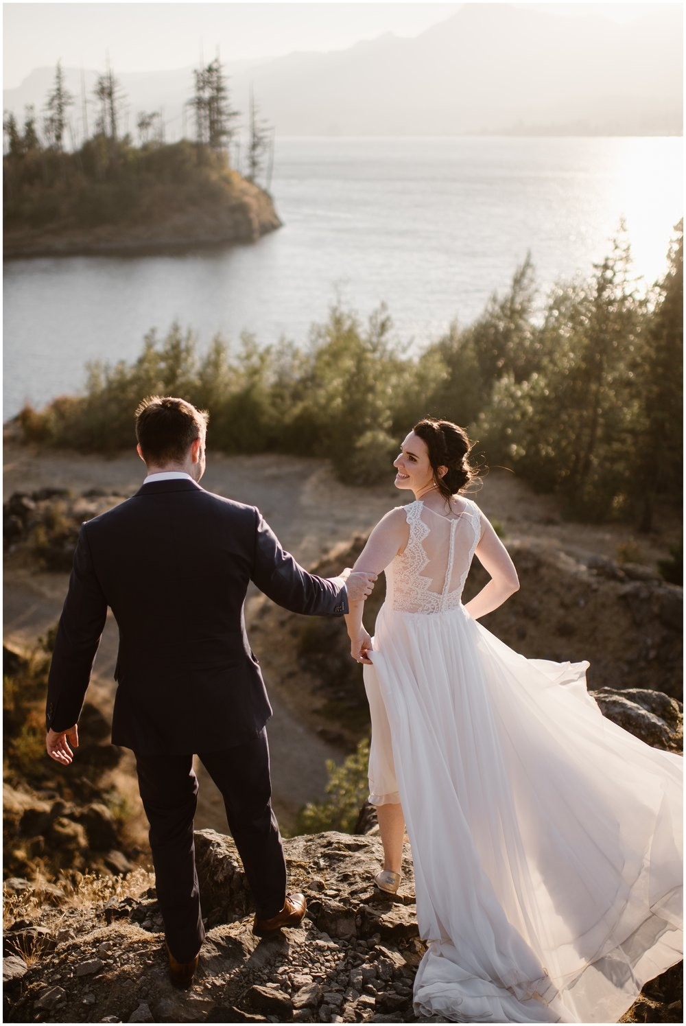 With their backs to the camera, Lauryn and David walk toward the edge of a cliff with the stunning Columbia River in the background. The two wanted to include some special exploring time on thei own after their family elopemet ceremony.