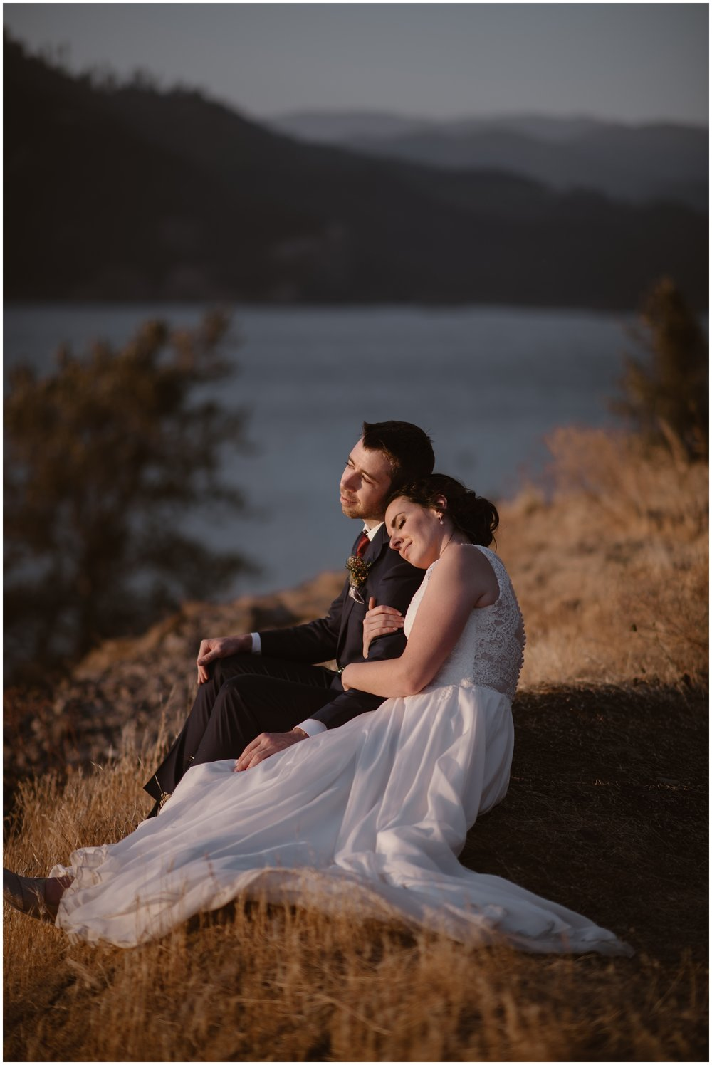 Lauryn and David take a moment to sit down in the golden grass as the sun sets on their elopement ceremony. Behind them, the Columbia River can be seen. The two hold each other close, reflecting on their small simple wedding.